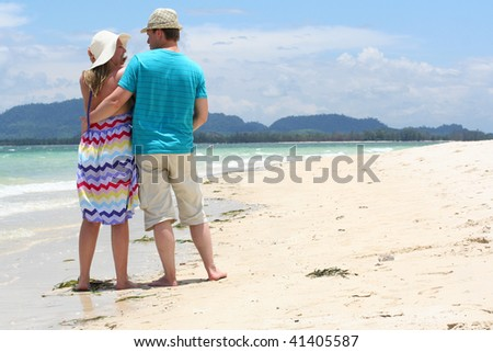 Young loving honeymooners on tropical sand beach - stock photo