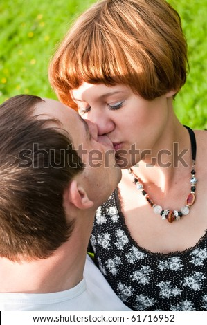Young loving kissing couple teens. Two Caucasian people. Teenagers: girl and boy embracing one another