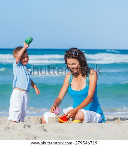 Young loving mother and her little son playing on the beach