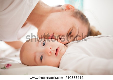 Young loving mother is kissing her baby boy on his cheek