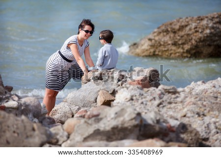 Young loving mother talking with her little son on a rocky seashore - stock photo