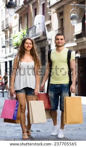 young loving pair with shopping bags at city street