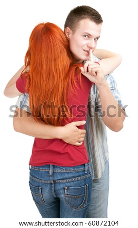 young loving people hugging each other, man keeping silent sign - stock photo