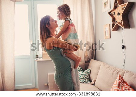 young loving pregnant mother having fun with toddler daughter at home - stock photo