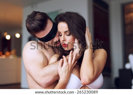 Young macho playing with sexy woman at home - stock photo