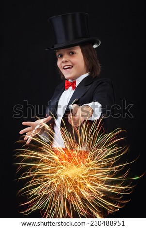 Young magician boy using his magic wand to conjure up sparks and fireworks - stock photo