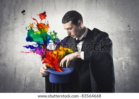 Young magician extracting colored paint from a cylinder hat - stock photo