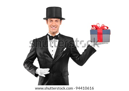 Young magician holding a magic wand and a gift isolated against white background - stock photo