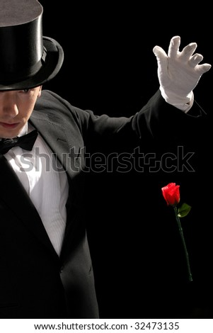 young magician performing red rose on black background - stock photo