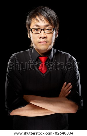 Young magician pose against dark background - stock photo