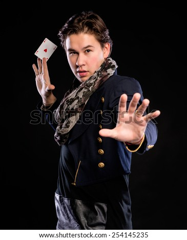 Young magician showing ace on a black background