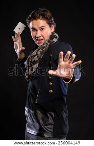 Young magician showing ace on a black background - stock photo