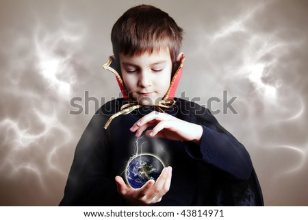 Young magician trying to save the Earth with his magic (focus on the hands/earth) - stock photo