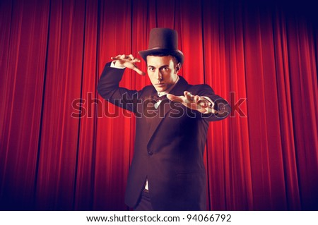 Young magician with curtain in the background - stock photo
