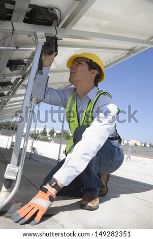 Young maintenance worker installing solar photovoltaic panels on rooftop - stock photo