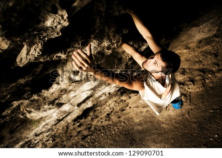 Young make climber doing a rock wall on a cave. - stock photo