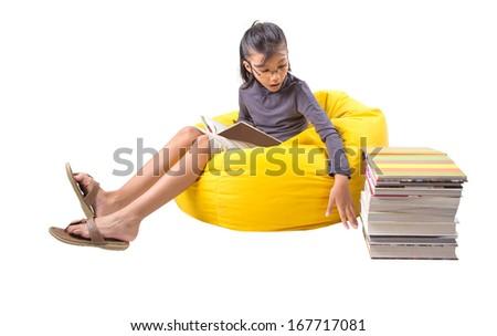 Young Malay Asian girl reading a book on a yellow bean bag - stock photo