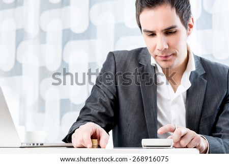 Young male accountant calculating earnings and profit while sitting at his desk with laptop computer. - stock photo