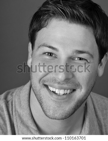 young male actor making emotional facial expression in front of camera