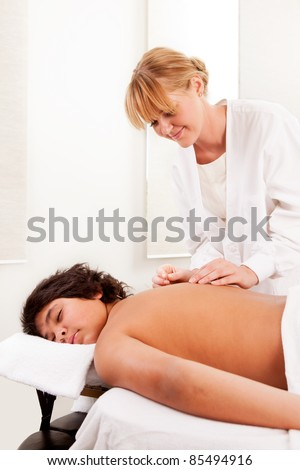 Young male acupuncture patient receiving treatment on back