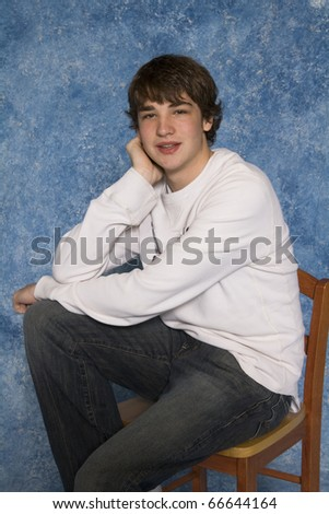 Young male adolescent in a casual pose sitting on chair and smiling - stock photo