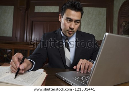 Young male advocate using laptop while preparing notes in courtroom - stock photo