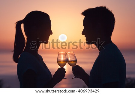 Young male and female enjoying a glass of wine on a tropical beach.  - stock photo