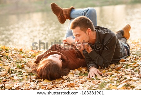 young male and female lying down near lake talking - stock photo