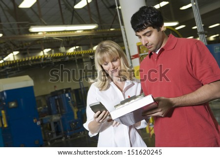 Young male and female make inventory in the newspaper factory - stock photo