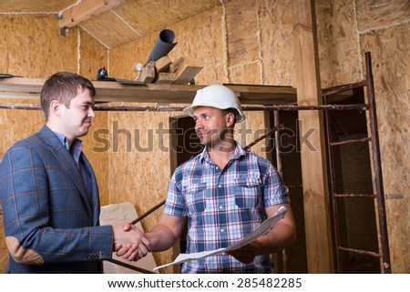 Young Male Architect and Construction Worker Foreman with Building Plans Shaking Hands Inside Unfinished House with Exposed Particle Plywood Boards - stock photo