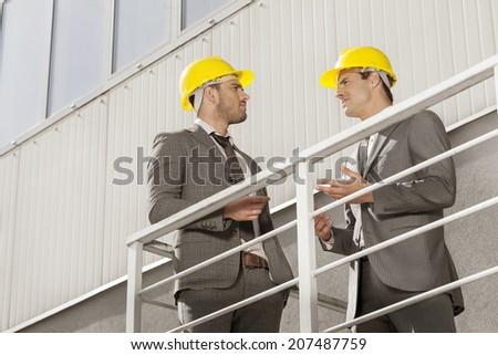 Young male architect discussing on stairway against building - stock photo