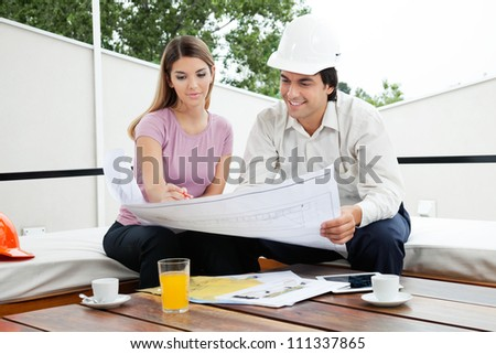 Young male architect having a discussion about house plans with female - stock photo