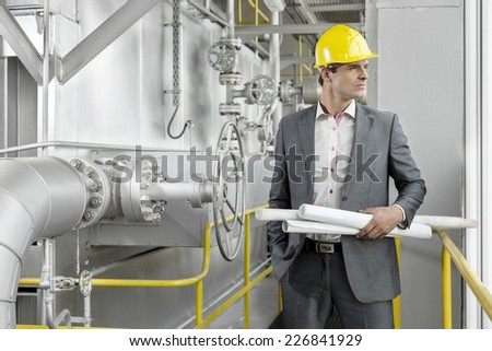 Young male architect holding rolled up blueprints by industrial machinery - stock photo
