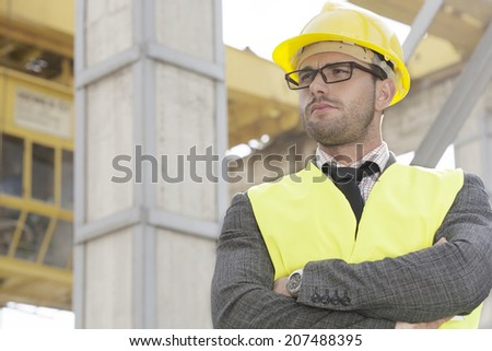 Young male architect standing arms crossed at construction site - stock photo