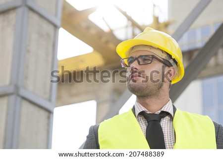 Young male architect wearing hard hat looking away at construction site - stock photo