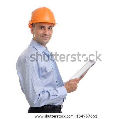 Young male architect wearing helmet and holding digital tablet pc - stock photo