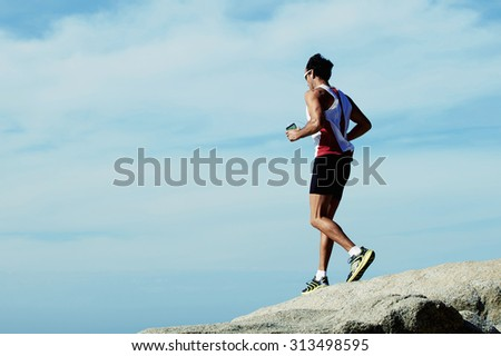 Young male athlete running down the rocks on the background of cloudy sky with copy space area for your text message or content, sportsman engaged in sports while listening to music in headphones - stock photo