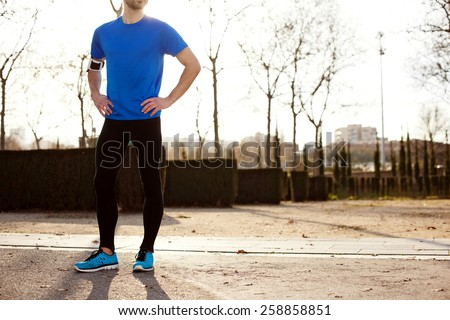 young male athlete standing in the park at sunset - stock photo