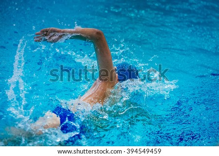 young male athlete swimmer in pool floats at competitions crawl - stock photo