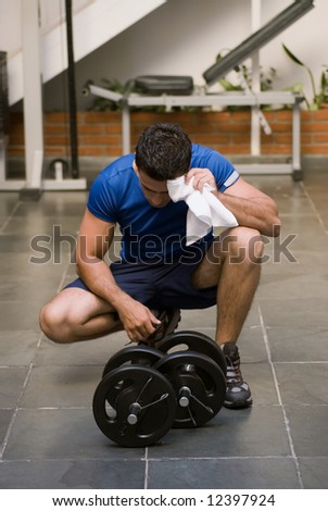 Young male athlete taking a break from lifting and wiping his head with a towel during a workout at the gym - stock photo