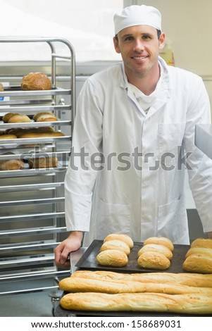 Young male baker standing in a kitchen in front of baguettes and rolls - stock photo