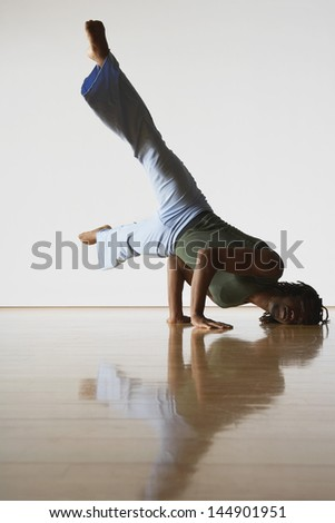 Young male ballet dancer doing handstand in rehearsal room - stock photo