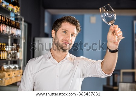 Young male bartender examining glass of wine in bar - stock photo