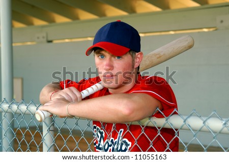 Young male baseball player poses with bat on his shoulder.  He is standing in dugout leaning on fence. - stock photo