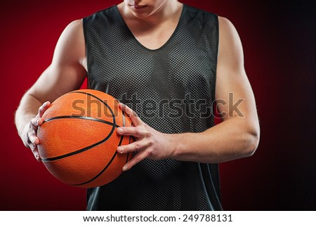 Young male basketball athlete gripping with two hands the ball tightly on red background - stock photo