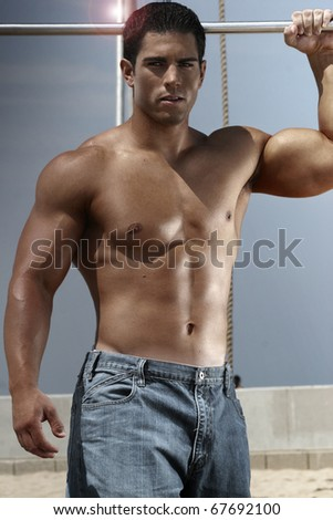 Young male bodybuilder in relaxed pose outdoors - stock photo