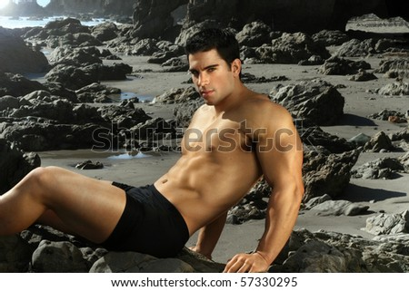 Young male bodybuilder laying on rocky shoreline - stock photo