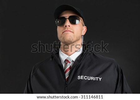 Young Male Bodyguard Wearing Sunglasses And Earpiece Over Black Background - stock photo