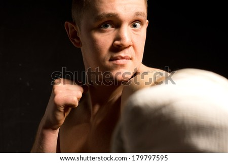 Young male boxer throwing a punch at the camera with a bandaged fist with a look of strong determination, focus to his face - stock photo