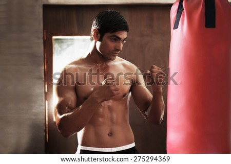Young male boxer working out with punching bag